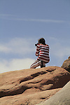 Young Hispanic woman taking a picture in Arches National Park, Utah, USA. .  John offers private photo tours in Arches National Park and throughout Utah and Colorado. Year-round.
