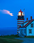 Lubec, Maine: West Quoddy Head Light in evening with light from the moonrise shimmering in the clouds
