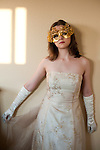 Teenager wearing a masquerade mask standing against a interior wall at sunset hoding dress fabric