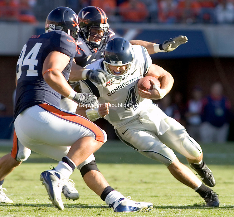 CHARLOTTESVILLE, VA- 13 OCT 2007- 101307JT18- <br /> UConn's Tyler Lorenzen gets tackled by Virginia's Allen Billyk, left, and Chris Long, center,after Lorenzen rushed 3 yards during the second quarter of Saturday's game at Virginia. UConn lost 16-17.<br /> Josalee Thrift / Republican-American