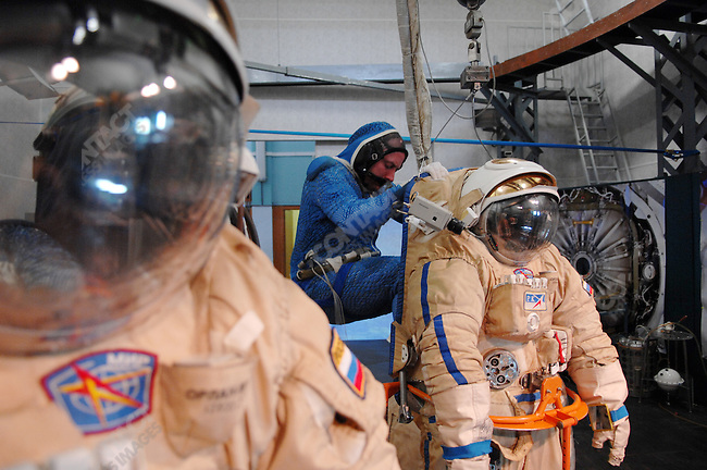 At one of the training centres at Star City, the Russian space training centre outside of Moscow, cosmonaut Yuri Lonchakov, commander of Soyuz 18, and astronaut Mike Fincke, ISS commander, dressed in water cooled under-suits, went through a programme in the Orlan-MK space suits simulating work on the Russian Segment Airlock on the International Space Station (Fincke with Blue Stripe on Suit/Lonchakov with Red Stripe on Suit), here finally exiting the suits after the end of the practice. Star City, Russia, June 24, 2008.