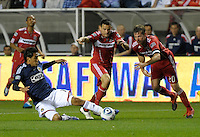 Chivas midfielder Jesus Padilla (10) slide tackles the ball away from Chicago midfielder Marco Pappa (16) and forward Brian McBride (20).  The Chicago Fire tied Chivas USA 1-1 at Toyota Park in Bridgeview, IL on May 1, 2010.
