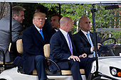 U.S. President Donald Trump, center left, and Emmanuel Macron, France's president, center, sit in a golf cart while touring outside the Mansion at the Mount Vernon estate of first U.S. President George Washington in Mount Vernon, Virginia, U.S., on Monday, April 23, 2018. As Macron arrives for the first state visit of Trump's presidency, the U.S. leader is threatening to upend the global trading system with tariffs on China, maybe Europe too. <br /> Credit: Andrew Harrer / Pool via CNP