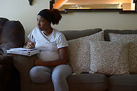 NWA Democrat-Gazette/ANDY SHUPE<br /> Sade Danie takes notes Friday, June 29, 2018, while studying with the help of a DVD at Compassion House in Elm Springs. Danie is the first 18-year-old woman to move into Compassion House, a home for pregnant teens, after a policy change made June 11 allowed them to accept 18- and 19-year-olds.