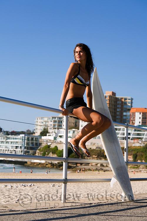 Surfer girl on the promenade at Bondi Beach.  Sydney, New South Wales, AUSTRALIA.
