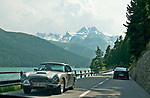 Classic car rides past Lake Sils in the Graubunden region headed towards St. Mortiz, Switzerland during the British Class Car Meeting, an annual event featuring: Rolls-Royce, Bentley, Aston Martin & Lagonda, Jaguar & Daimler, and Austin-Healey & Healey and a limited number of pre-1960 British cars