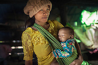July 29, 2014 - Mondulkiri (Cambodia). A Phnong mother with her baby pose inside a traditional house in Busra village. © Thomas Cristofoletti / Ruom