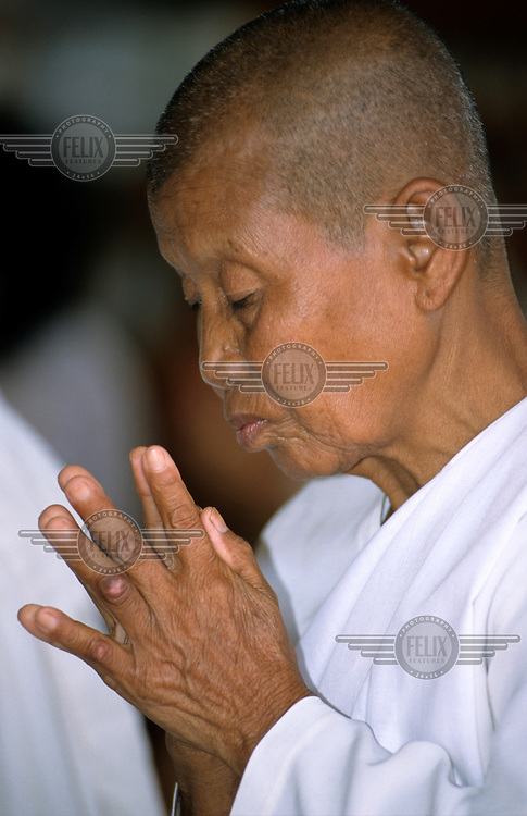 An old woman praying during a Buddhist ceremony.