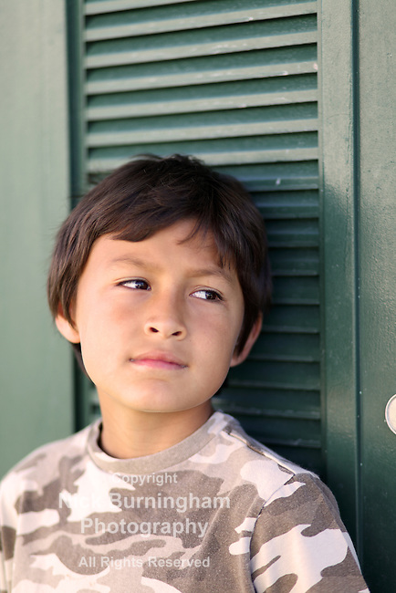 Young serious boy looks to his left leaning on a door - EXCLUSIVELY AVAILABLE HERE