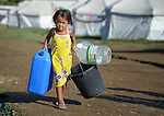 Heart Bunda, a 4-year old girl displaced by Typhoon Haiyan in November 2013, carries water containers to fill in a temporary shelter at the West Campus of the Northern Iloilo Polytchnic State College in Estancia, Philippines. The storm was known locally as Yolanda. Residents of this camp have been assisted by the ACT Alliance. More than 100 families remained in the camp in February 2014, many of them refusing to return to a coastline soaked by an oil spill during the typhoon, and uninterested in a government offer to relocate them at a remote location well out of the city.