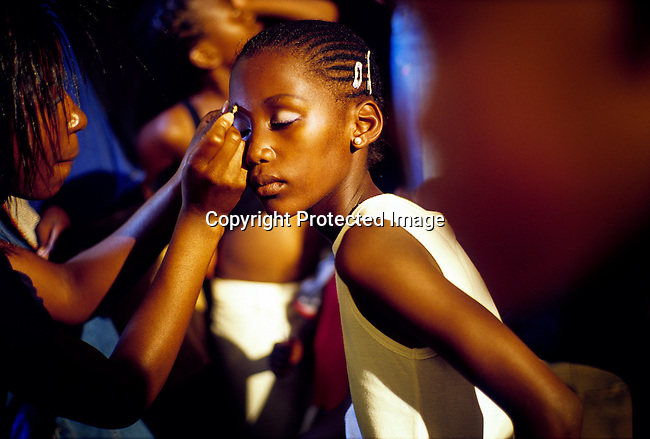 A girl gets a makeup backstage before a beauty competition on December 20, 2004 in Soweto, Johannesburg, South Africa. Soweto, the biggest township in South Africa, has a population of about 3.5 million. A growing number of people belong to a new black middle-class and elite in the country, and they have money to spend on beauty, and clothes. Many have risen from poverty in the townships to a different lifestyle, since the fall of Apartheid and the start of democracy in the country in 1994.