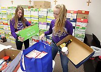 Guerin students helped fill food boxes at St. Maria Goretti for distribution at Thanksgiving.  (l-R) Sami Bischof and Hannah Miller.