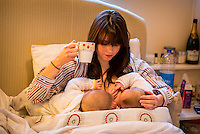 "A woman breastfeeding 5 month old twins at the same time on her bed in her bedroom while drinking a cup of tea.<br /> <br /> Image from the ""We Do It In Public"" documentary photography project collection: <br />  www.breastfeedinginpublic.co.uk<br /> <br /> Hampshire, England, UK<br /> 11/02/2013"