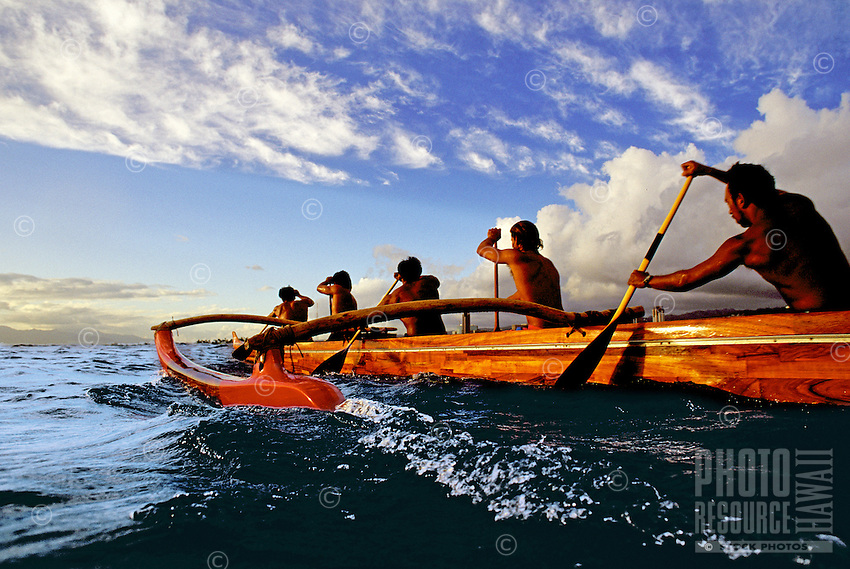 Paddlers in a koa canoe off Waikiki Beach on a beautiful afternoon, photographed from water level.