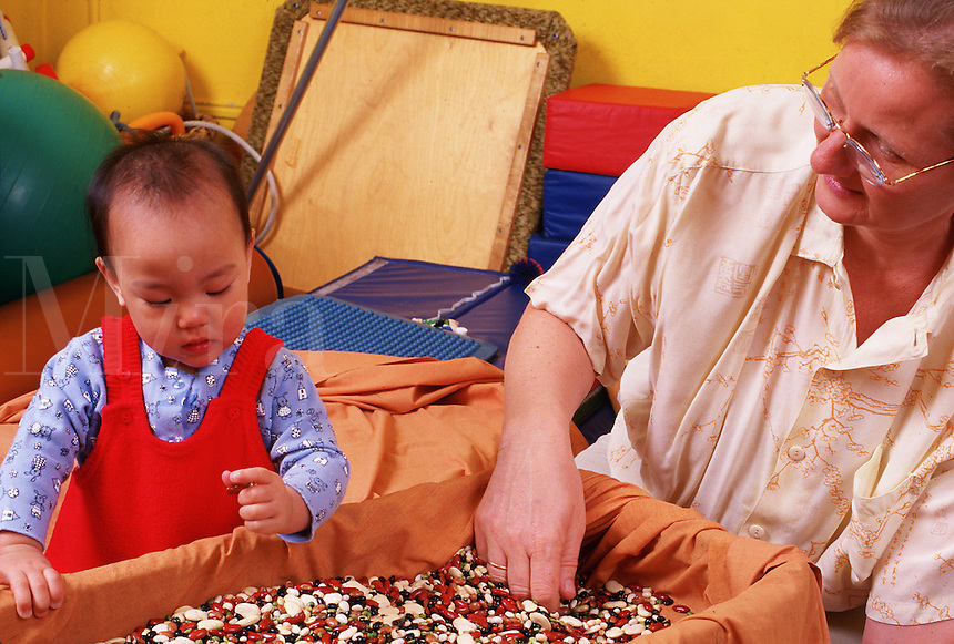 A teaching assistant and young child examine a box of confetti