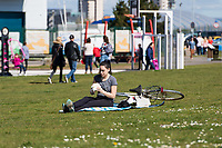 CARDIFF, UK. 2nd April 2017. A young woman relaxed in sunny weather in Cardiff Bay
