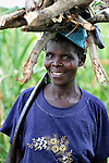 "A woman returns from gathering firewood near Chisatha, a village in southern Malawi. Her community has been hard hit by drought in recent years, leading to chronic food insecurity, especially during the ""hunger season,"" when farmers are waiting for the harvest. The ACT Alliance is working with farmers in this village to switch to alternative, drought-resistant crops, such as millet, as well as using irrigation and other improved techniques to increase agricultural yields. Solar panels will power a pump that will draw water from a river into a reservoir and then into six elevated 5,000 liter tanks, which will then provide water to grow healthy crops year round."