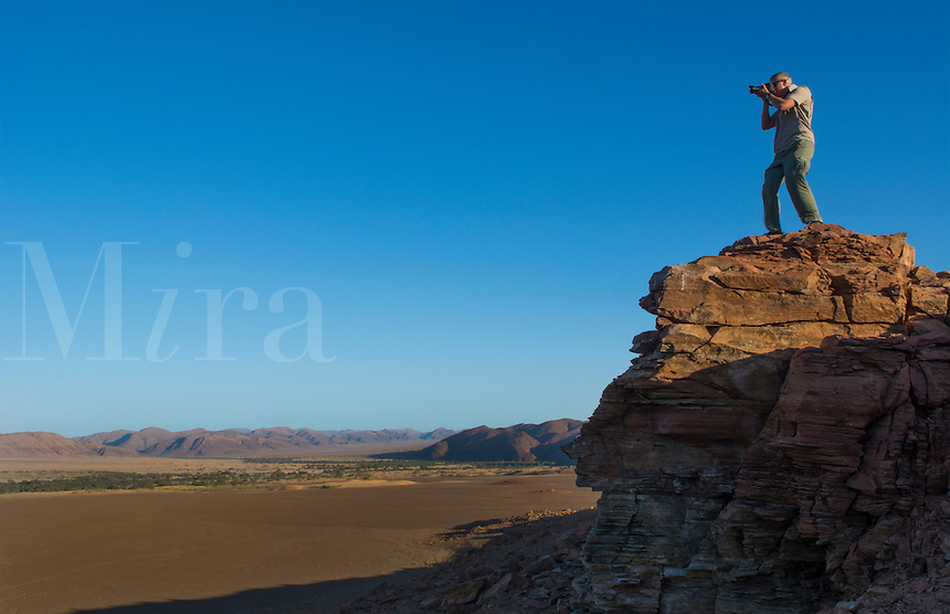 Namibia Africa photographer on cliff shooting pictures in Puros desert near the Okahirongo Elephnat Lodge