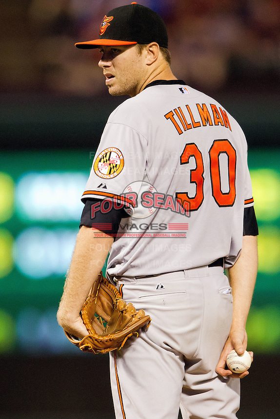 Baltimore Orioles pitcher Chris Tillman #30 looks in for the sign during the Major League Baseball game against the Texas Rangers on August 21st, 2012 at the Rangers Ballpark in Arlington, Texas. The Orioles defeated the Rangers 5-3. (Andrew Woolley/Four Seam Images).