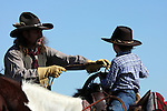 A cowboy on horseback showing his son how to throw a rope to catch cattle