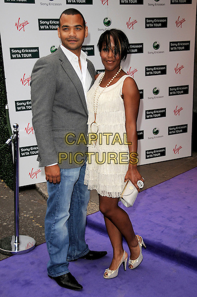MICHAEL UNDERWOOD & ANJELLICA BELL.The WTA Tour Pre-Wimbledon Party,  Kensington Roof Gardens, London, England..June 18th, 2009.full length Anjellica Anjelica angelica grey gray suit jacket jeans denim white cream tassels dress clutch bag couple .CAP/CAS.©Bob Cass/Capital Pictures.