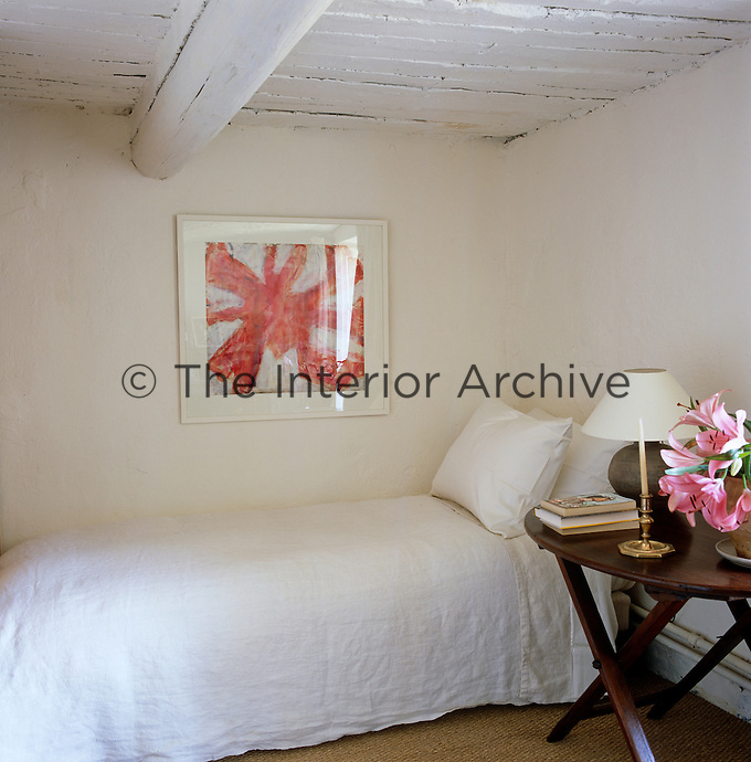 In the simple white guest bedroom the bed is covered with 19th century French linen