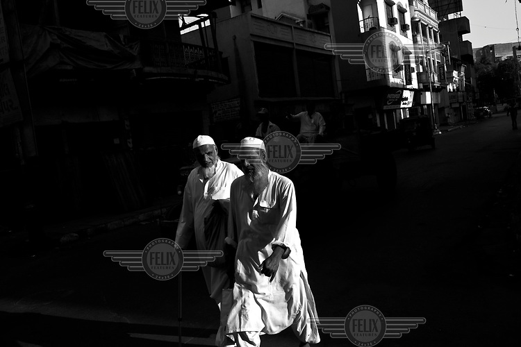 Two men, caught in a shaft of sunlight, walk through the old city of Ahmedabad.