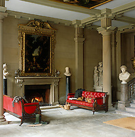 "Two red leather sofas flank the fireplace in the North Entrance Hall, which was the kitchen until the 1760s. ""Diana and her Nymphs surprised by Actaeon"", 1650's, by Maratti and Dughet hangs above the fireplace"
