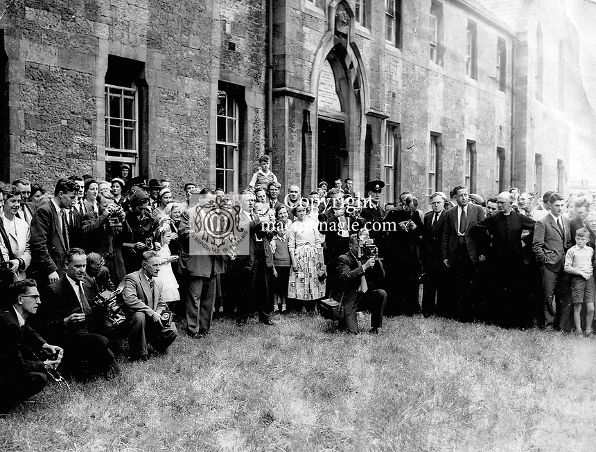 Killarney photographer Donal MacMonagle Irish Press Photographer (grey suit standing about a third of the way from left) reloads his glass plates at a press event in the 1960's while his brother Louis, The Cork Examiner, kneels and composes his frame (centre) at an event in Limerick in the 1950's..Picture by Harry MacMonagle