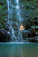 Man sitting in meditation position relaxes under a waterfall.