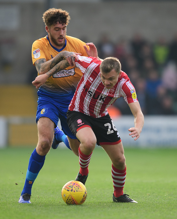 Lincoln City's Harry Anderson shields the ball from Mansfield Town's Ryan Sweeney<br /> <br /> Photographer Chris Vaughan/CameraSport<br /> <br /> The EFL Sky Bet League Two - Lincoln City v Mansfield Town - Saturday 24th November 2018 - Sincil Bank - Lincoln<br /> <br /> World Copyright © 2018 CameraSport. All rights reserved. 43 Linden Ave. Countesthorpe. Leicester. England. LE8 5PG - Tel: +44 (0) 116 277 4147 - admin@camerasport.com - www.camerasport.com