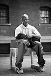 """TYRONE AND HAPPY, A 4-MONTH-OLD LABRADOR RETRIEVER -- Tyrone has been sentenced to 8 1/2 years and has served 5 years for threatening someone at gunpoint. TYRONE: """"Socrates said, """"Sonte walls do not a prison make, nor iron bars a cage."""" I've learned not to let these walls make me a prisoner of my own emotions. The program has  taught me to be patient, honest with myself, and how to work without ego. My last dog, Yankee, went to a war veteran somewhere in Colorado. Just knowing that I helped to change someone's live makes me feel as if I have a purpose and a destiny.  These dogs have a way of touching a person's spirit."""" ..The Puppies Behind Bars (PPB) Program works with prison inmates in New York, New Jersey, and Connecticut to train service dogs, including ones who help injured soldiers. The puppies arrive at 8 weeks-old and remain at the prisons, mostly working with one inmate, for 20 months. Fishkill Correctional Facility is a medium security prison in New York with 22 men in the puppy program. The emotional element of caring for the puppies breaks down the hard façade that most prisoners create for themselves to survive prison life.  Prisoners learn responsibility and pride in helping others. The program often gives them a new outlook on their crimes, their time in prison, and goals when they are released. .."""