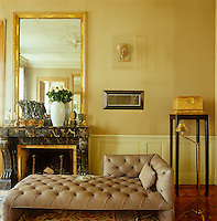 In the salon to one side of the ornate 18th century marble fireplace an Egyptian mask hangs above a small graphite work by Brice Marden whilst the padded leather chaise longue is an Ed Tuttle design