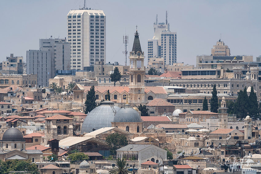 The Christian Quarter of the Old City of Jerusalem with the gray dome of the Sisters of Zion Convent at left.  In the center are the two domes of the Church of the Holy Sepulchre with the tall bell tower of the Church and Monastery of Saint Saviours behind.  The Old City of Jerusalem and its Walls is a UNESCO World Heritage Site.