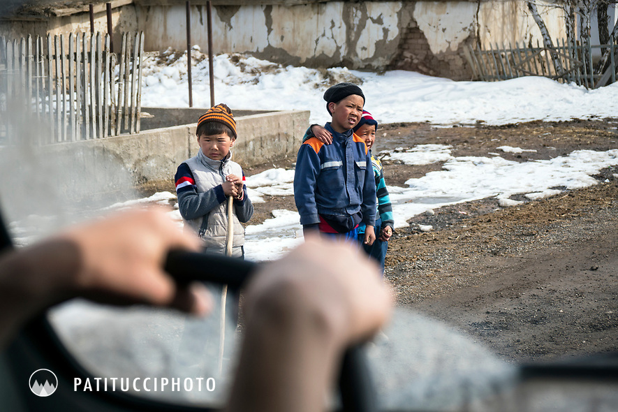 The view through the front window of a car while driving through Kyrgyzstan. Children playing on a road.