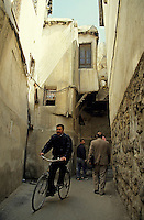 Man cycling through the narrow streets of the old town, Damascus, Syria.