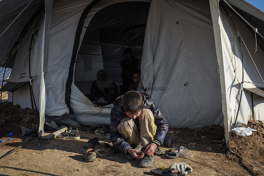IRAK, Bashika: One of the children of the Khamsa family put his shoes on in front of his small tent. He and his family  just arrived from Mosul in Bashik  where they have to wait to be transfered to a IDP camp, the 11th December 2016. <br /> <br /> <br /> IRAK, Bashika: Un des enfants de la famille Khamsa met ses chaussures devant sa petite tente. Lui et sa famille viennent d'arriver de Mossoul &agrave; Bashik o&ugrave; ils doivent attendre pour &ecirc;tre transf&eacute;r&eacute;s dans un camp de d&eacute;plac&eacute;s, le 11 d&eacute;cembre 2016.