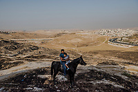 Mohammad al-Eisawi, 39, and his son Majd, 5, sit atop of an Arabian pure breed horse, named Furys, above the neighborhood of Essawiya on June 07, 2016 in East Jerusalem. <br /> Photo Daniel Berehulak for the New York Times