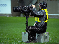 Heavily weatherproofed photographer Marty Melville chimps during the Super Rugby quarterfinal match between the Hurricanes and Sharks at Westpac Stadium, Wellington, New Zealand on Saturday, 23 July 2016. Photo: Dave Lintott / lintottphoto.co.nz