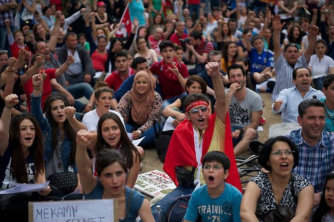 Bis zu 700 Menschen beteiligten sich am Sonntag den 9. Juni 2013 auf dem Oranienplatz in Berlin-Kreuzberg an eine &quot;Sitzdemonstration&quot;. Sie sangen populaere tuerkische Lieder, die zum Teil mit regierungskritischen Texten neu interpretiert wurden. Trotz einsetzendem Wolkenbruch wurde gesungen, getanzt und gefeiert.<br />9.6.2013, Berlin<br />Copyright: Christian-Ditsch.de<br />[Inhaltsveraendernde Manipulation des Fotos nur nach ausdruecklicher Genehmigung des Fotografen. Vereinbarungen ueber Abtretung von Persoenlichkeitsrechten/Model Release der abgebildeten Person/Personen liegen nicht vor. NO MODEL RELEASE! Don't publish without copyright Christian-Ditsch.de, Veroeffentlichung nur mit Fotografennennung, sowie gegen Honorar, MwSt. und Beleg. Konto:, I N G - D i B a, IBAN DE58500105175400192269, BIC INGDDEFFXXX, Kontakt: post@christian-ditsch.de<br />Urhebervermerk wird gemaess Paragraph 13 UHG verlangt.]