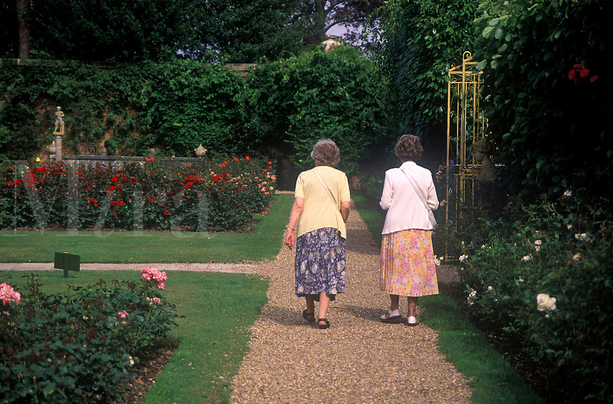 Two elderly ladies walking along garden pathway in Hever Castle Garden.  Hever Castle was home of Ann Boleyn, Henry VIII's 2nd wife.  Edenbridge, Kent, UK