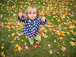 Toddler on wet fall afternoon reaching up to be lifted with hands raised.