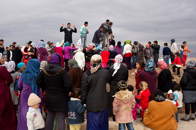 DOMIZ, IRAQ: Syrian refugees crowd around a group handing out aid in the Domiz refugee camp in the Kurdish region of northern Iraq...The semi-autonomous region of Iraqi Kurdistan has accepted around 60,000 refugees from war-torn Syria. Around 20,000 refugees live in the Domiz camp which sits 60 km from the Iraq-Syria border...Photo by Younes Mohammad/Metrography