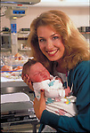 smiling nurse holding infant in hospital nursery