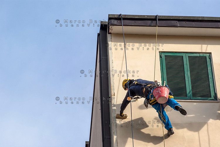 Milano, periferia nord, ristrutturazione della facciata di un palazzo. Imbianchino lavora sospeso da funi --- Milan, north periphery, renovation of a building's facade. Painter suspended from ropes