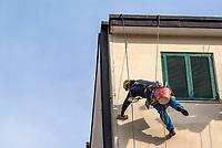 Milano, periferia nord, ristrutturazione della facciata di un palazzo. Imbianchino lavora sospeso da funi --- Milan, north periphery, renovation of a building's facade. Painter suspended from ropes