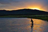 The July sun sets over Island Park, Idaho as this fisherman casts for fat Henry's Fork rainbow trout.