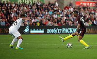 Raheem Sterling of Manchester City (R) dribbles his way past Kyle Naughton of Swansea City to score the third for his team during the Premier League match between Swansea City and Manchester City at The Liberty Stadium in Swansea, Wales, UK. Saturday 24 September 2016