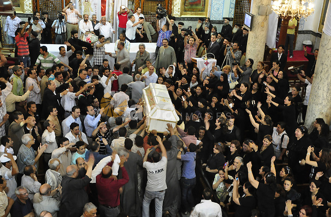 "Egyptian Coptic Christians carry the coffin of a victim of sectarian clashes during a funeral in Cairo on May 8, 2011 as Egypt's military rulers warned they will use an ""iron hand"" to protect national security after clashes between Muslims and Christians in the Egyptian capital killed 12 people and injured scores.  Photo by Ahmed Asad"