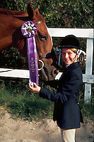 Young girl, horse, and first-place ribbon at horse show